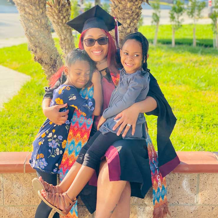 Kwashae Ruffin in academic regalia with two of her daughters on her lap.
