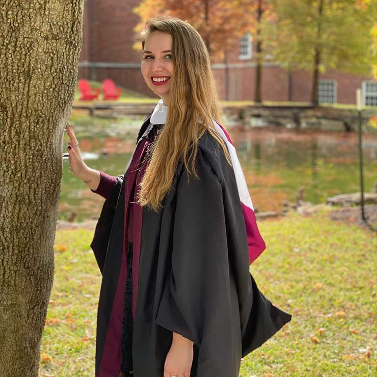 Regan Campbell in her academic regalia standing outdoors near the library on the TWU Denton campus.