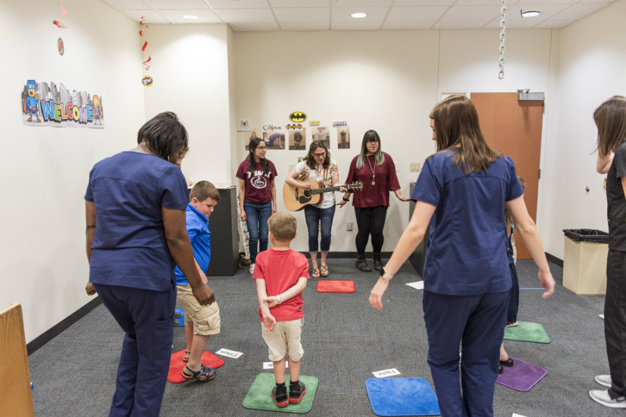 A woman playing the guitar to a group of dancing kids in the clinic with nurses around.