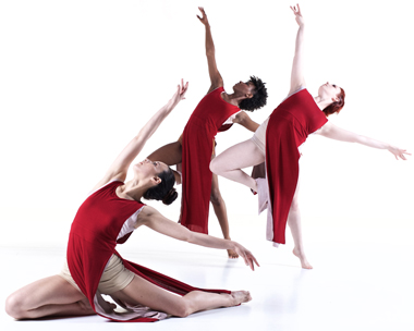 3 female dancers pose in red costumes with arms outstretched