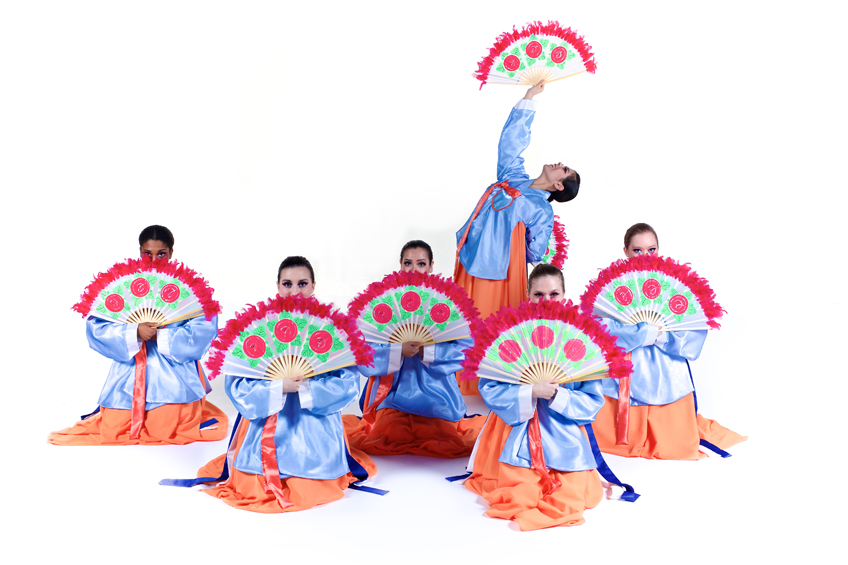 Six student folklorico dancers dressed in brightly colored costumes with fans