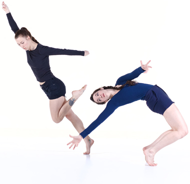 Two dancers wearing dark colors in modern dance poses