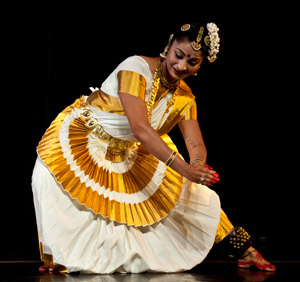 Photo of Anisha Rajesh dancing in a white and bright yellow costume