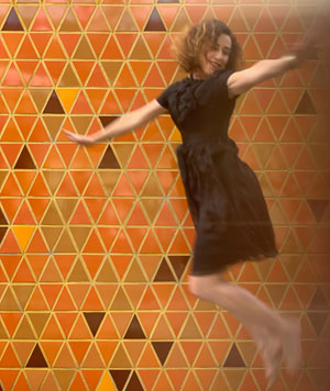Robin Conrad dancing in front of a retro tile pattern