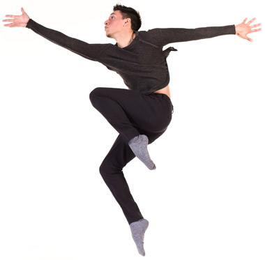 Male student dressed in black leaps into the air
