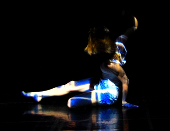 Modern dance student performs solo under blue lights