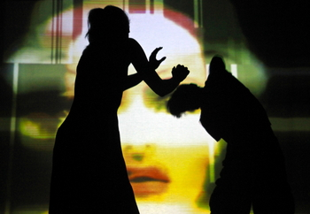 2 students dance in silhouette in front of a projected image of a face