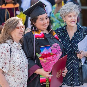 A graduate wearing a special cultural stole with her cap and gown stands with her mother and grandmother on either side of her