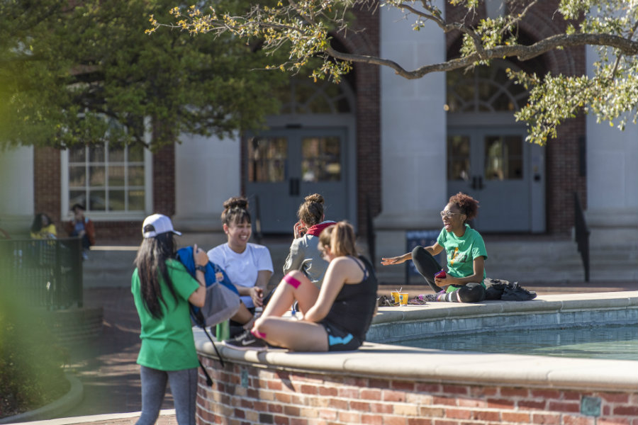 A group of students on a sunny day sitting around the fountain on TWU's Denton campus.