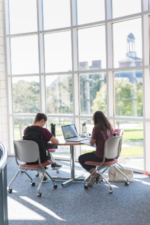 Two young women study at a table in Pioneer Hall with the Library visible out the window.