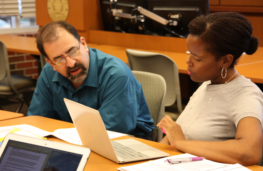 Assistant professor Gray Scott, Ph.D., works with a graduate student during a rhetoric class.
