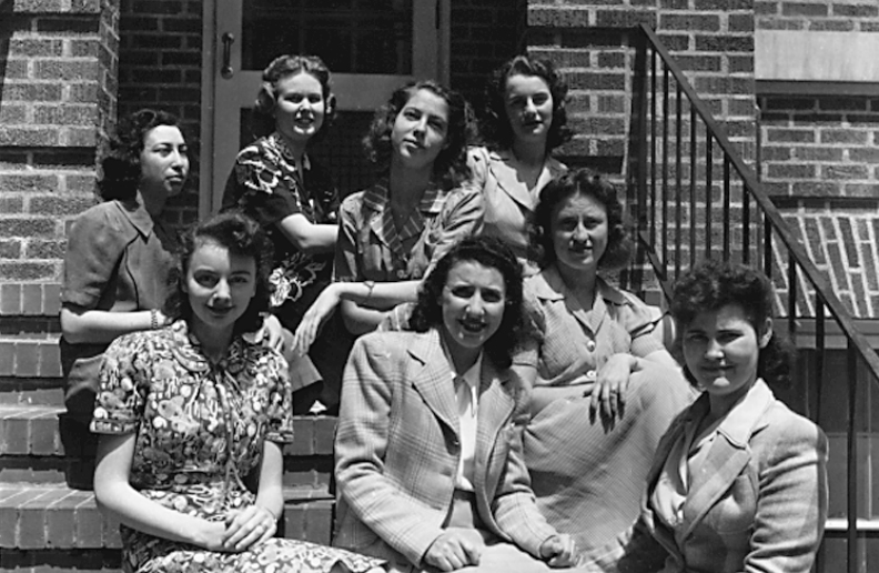 Group of girls sitting on a staircase in black and white photo.