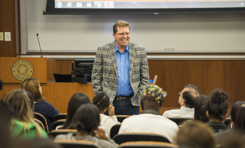 Associate professor of English Brian Fehler, Ph.D., lectures during a presidential debate watch on campus.