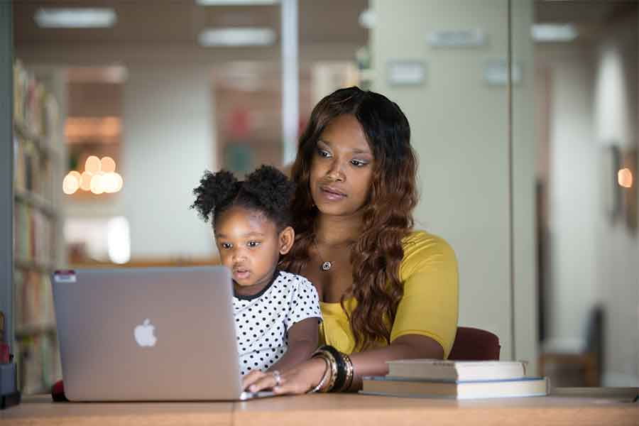 A woman works on a computer with her child in her lap.
