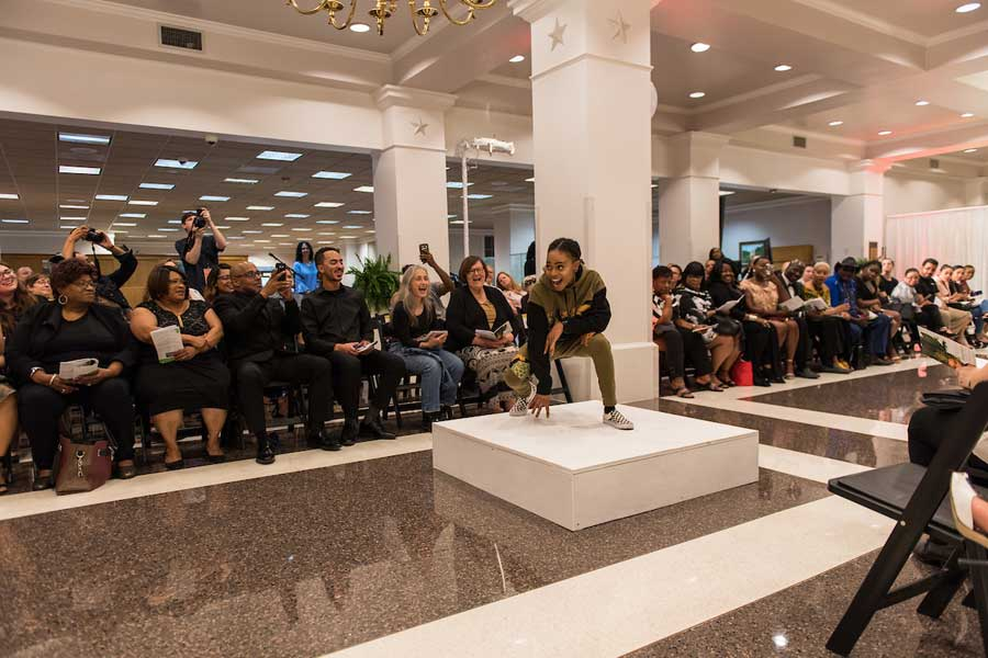 Streetwear model poses in crouched position on the runway