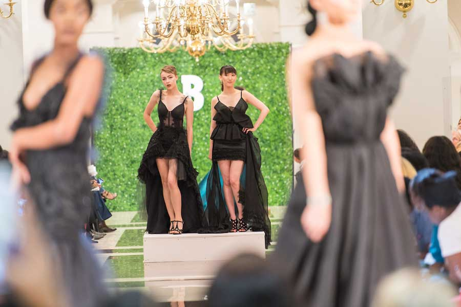 Models in black gowns on the runway