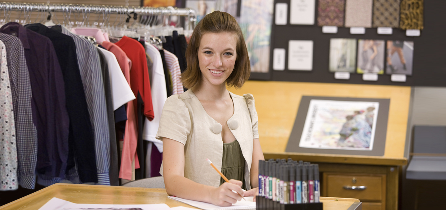 Fashion Merchandising student works at a table with clothing in the background.