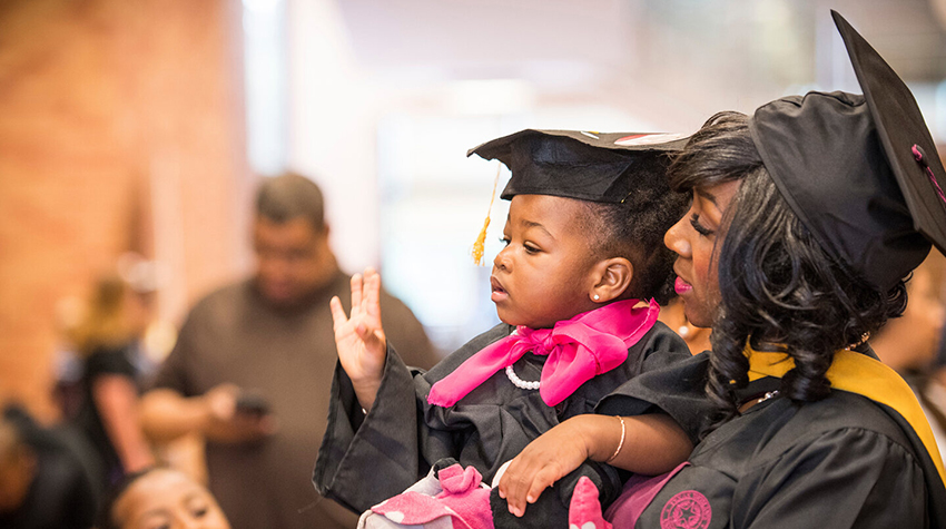 A graduate holds her young daughter, also dressed in graduation regalia.