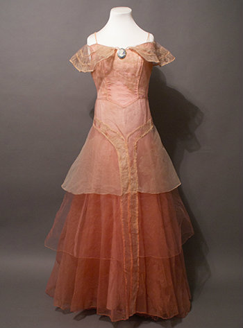 The full dress is shown. It begins with a light pink that transitions to red with layers of chiffon.