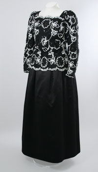 A black mid-length dress with long sleeves and white embroidery along the top half of the dress.