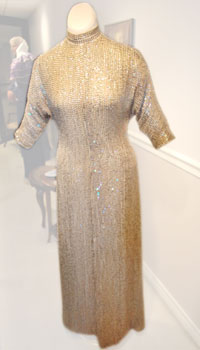 A sequin-covered silk chiffon gown with a mandarin collar and fitted three-quarter length sleeves.