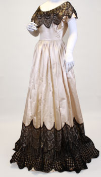 A heavy ivory satin dress with black Spanish lace trim circling the skirt and shoulders.