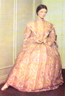 Dress made of sheer muslin with a full skirt, high neckline, double bell sleeves, and fitted bodice.