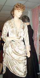 An ivory satin brocade dress draped over a black satin skirt on a mannequin.