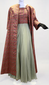 A gown with a light green silk skirt and red plaid top with a matching red plaid long coat.
