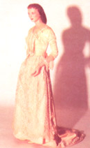 A long, light pink dress is shown with mid-length sleeves and lace trim.
