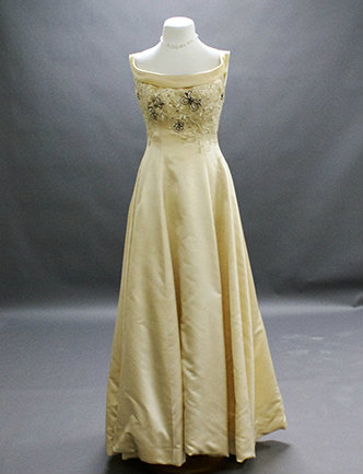 A white silk satin gown with appliquéd beading of crystals, pearls and rhinestones.