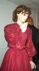 A long-sleeved red dress with a V-neck and tight bodice shown from the waist up.