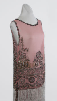 A sleeveless orchid colored dress with floral embellishments and a fringe trim along the bottom.