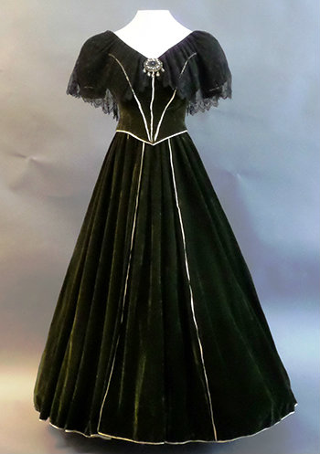 The gown on a dress form. Green velvet with a full bottom and white satin piping the skirt and seams