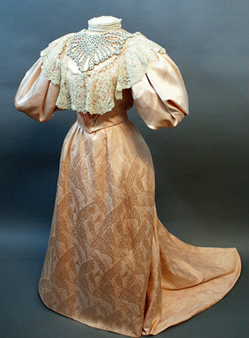 The full gown is shown on a dress form. It is a light salmon taffeta brocade with a lace collar.