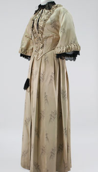 A soft beige brocaded dress with a long hoop skirt, fitted waist, and wide elbow-length sleeves.