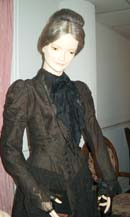 A long-sleeved black lace over black taffeta dress is shown on a mannequin from the waist up.