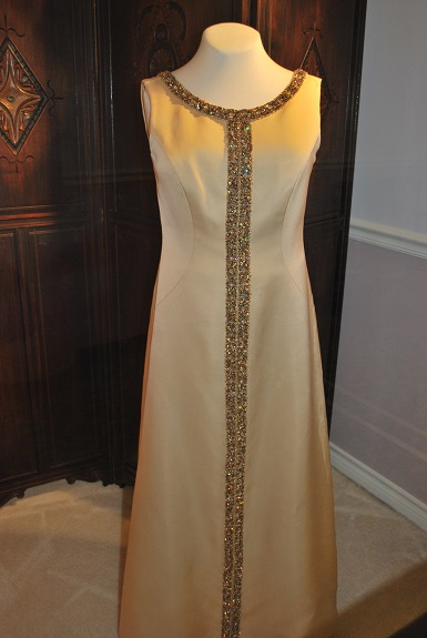 The full sleeveless cream silk gown is shown with jeweled embellishments down the front and neckline