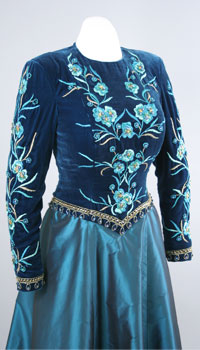 A teal skirt and a navy blue bodice that is decorated with a floral motif embroidery.