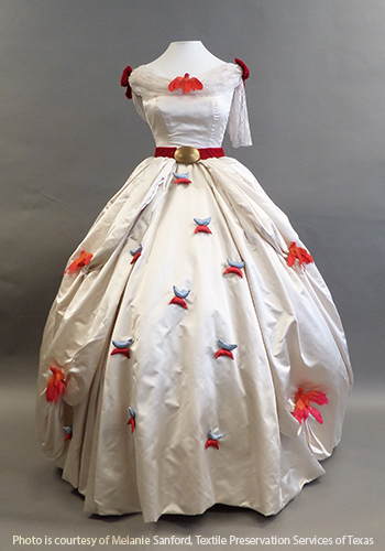 White satin dress with scattered red flowers on the skirt and a red velvet belt at the waist.