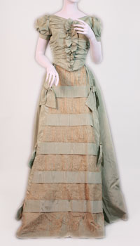 The dress is made of turquoise moiré taffeta trimmed with bows and has lace inserts on front panel.