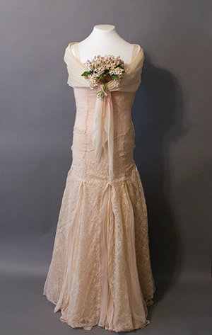 A pink lace gown with a fitted bodice and fun skirt. A deep fichu covers the shoulders.