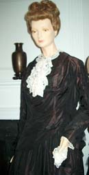 The long-sleeved black gown is shown on a mannaquin from the waist up. It has a white lace collar.