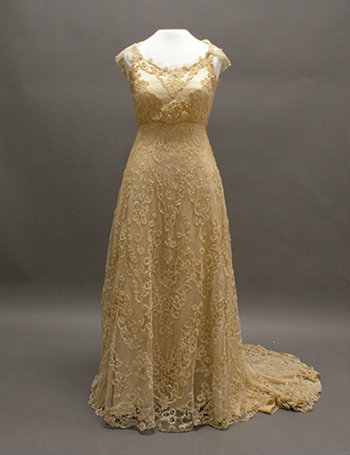 The full gown is shown on a dress form. It is a gold lace with cap sleeves.