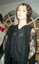 The dress shown from the waist up. Made of black satin brocade with a cowl drape at the neckline.