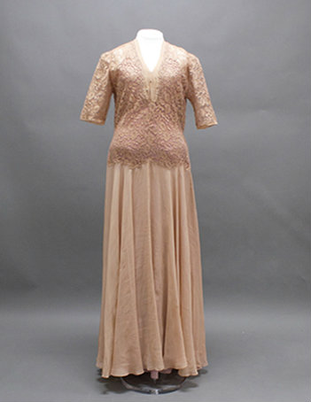 A cream colored dress with a V-neck and mid-length sleeves. The bodice is covered in a cream lace.