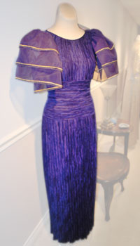 A purple silk chiffon gown with an accordion pleated skirt and three-tiered bell sleeves.