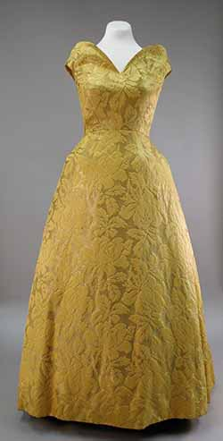 A long, gold brocade dress is shown on a dress form. It has cap sleeves and a natural waistline.