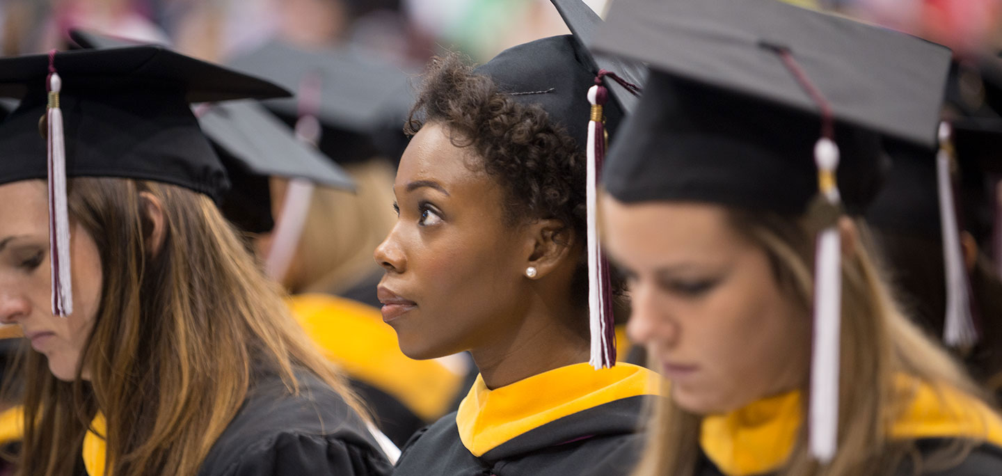 Three graduates sit during the commencement ceremony