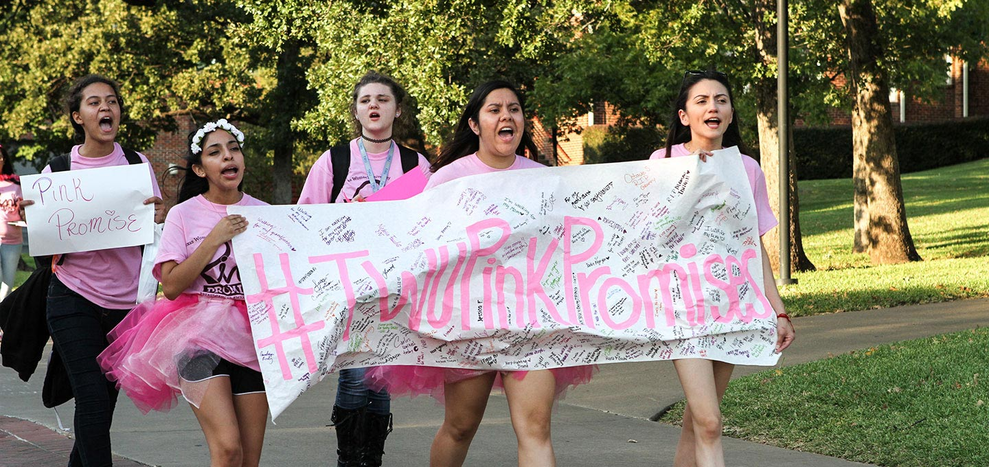 A group of students march on campus with a banner that reads #TWU Pink Promises